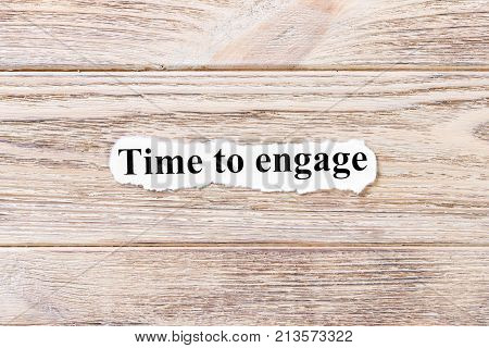 time to engage of the word on paper. concept. Words of time to engage on a wooden background.