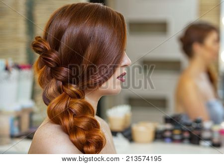 Beautiful girl with long red-haired hairy. hairdresser weaves a French braid close-up in a beauty salon. Professional hair care and creating hairstyles.