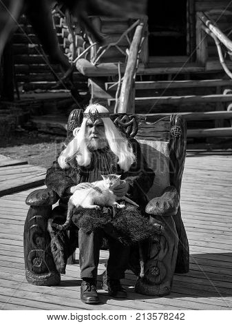 Druid old man with long grey hair beard with crown in fur coat holds cat and sits in wooden chair on log house background