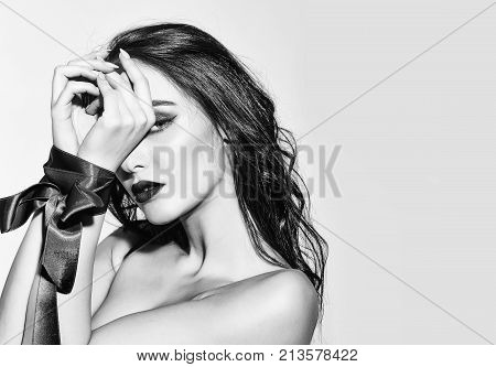 pretty woman or cute sexy girl in erotic bra with long curly brunette hair has red lips makeup on adorable face and ribbon bow on hands isolated on white background copy space