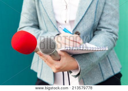 Female journalist taking notes and holding microphones at news conference