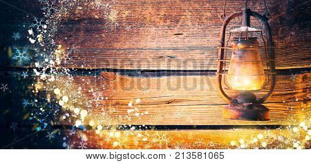 Vintage oil lamp over Christmas holiday wooden planks rural background. Beautiful Empty Christmas Backdrop decorated with snow. New Year Background. Magic light, Xmas background