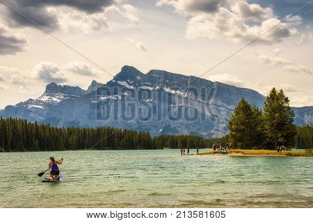 TWO JACK LAKE, ALBERTA, CANADA - JUNE 26, 2017 : Tourists enjoy a sunny day at the two jack lake in Banff National Park with Mt. Rundle in the background.