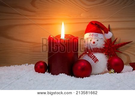 Christmas snowman with red scarf and santa claus hat , isolated on wood background.Advent candle and Snowman.Happy New 2018 Year background.