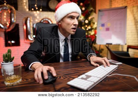 Businessman In The Office On New Year's Eve. He Enthusiastically Plays On The Computer.