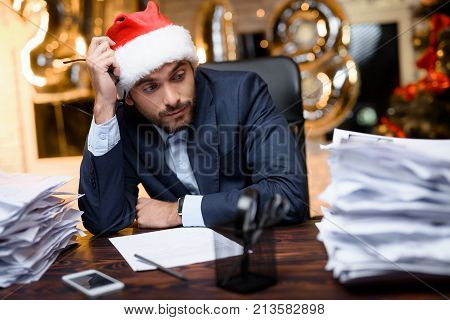 Businessman In The Office On New Year's Eve. Around Him A Bunch Of Different Forms And Reports.