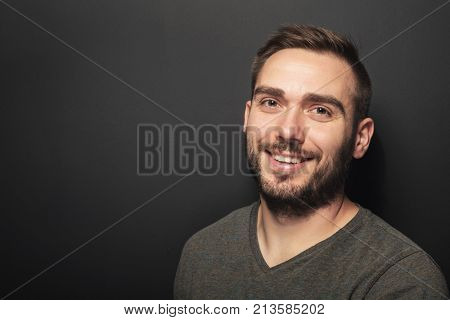 Good-looking dark-haired man in his 30s smiling and looking happy. Casual portrait on black background