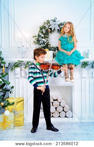 Elegant nine year old boy playing the violin Christmas melodies to a cute girl. Inspiration. Romantic Christmas night.