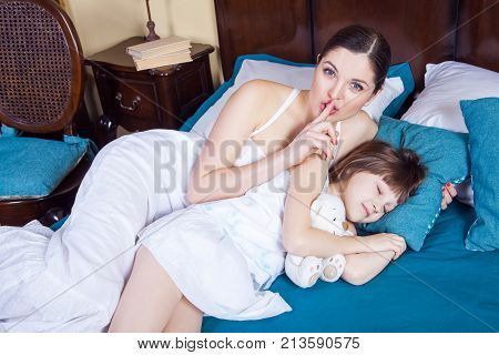 Mother And Daughter In Bedroom. Mother Showing Hash Sign At Camera, Daughter Closed Eyes And Sleepin