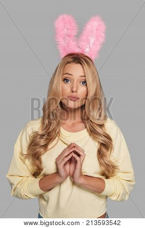 Pure innocence. Attractive young woman in pink bunny ears keeping hands clasped and looking at camera while standing against grey background