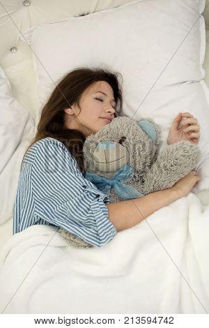 teen girl hugs teddy bear while sleeping