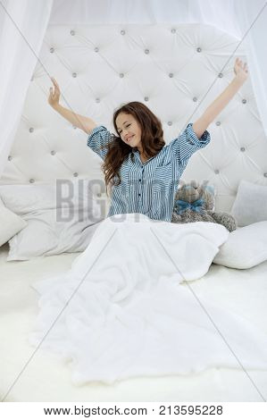 girl stretching her arms in bed in the morning in a white bedroom