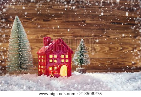 Old wooden planks with christmas trees and red house. Brown background with snow and snowflakes