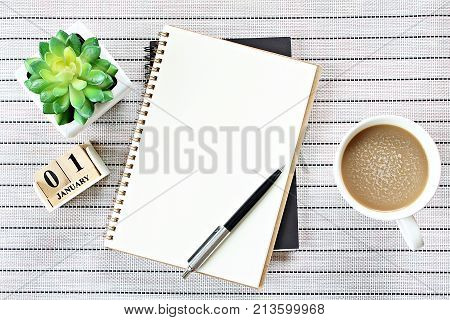 Business, weekend, holiday or new year planning concept : Top view or flat lay of open notebook paper, cube calendar and coffee cup on table background, ready for adding or mock up