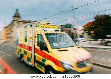 Prague, Czech Republic. Moving With Siren Bright Yellow Emergency Ambulance Reanimation Van Car On Street. Ambulance Car In Blurred Motion Background poster
