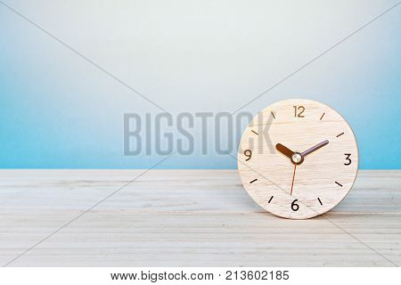 Business, savings time, deadline or delay concept : wooden alarm clock on white background