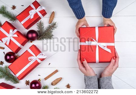 Son giving christmas gift to mum top view. Holidays present childhood and happiness concept. Close up of child and mother hands with gift box on white background. Christmas family traditions