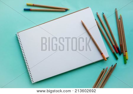 An empty sheet of sketchbook or album for drawing on a pink, blue background. Drawing a still life. Flat lay stock photo. Creativity concept