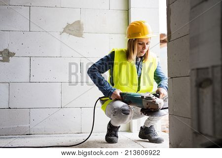 Female worker on the construction site. Beautiful young woman working with electric tool.