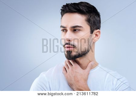 Strange feeling. Attentive serious young man looking worried about his health while standing and touching the neck with his fingers poster
