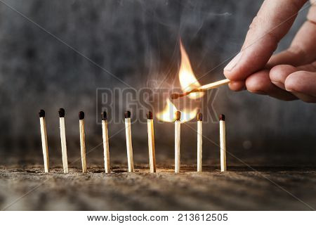 matches stand in a row one match burns. a human sets one match on fire. Concept of the idea. Top place for text