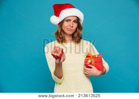 Impudent woman in sweater and christmas hat holding big gift box and giving small gift at camera over blue background