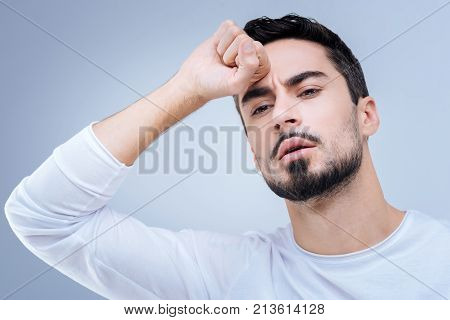 How strange. Handsome young bearded man standing with his fist near the forehead while thinking about a strange unusual situation at work