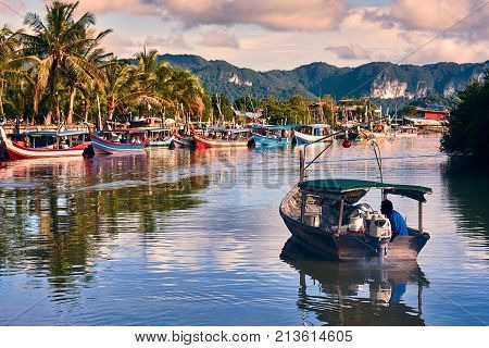 A local fisherman goes out on a boat from boats park to the sea for fishing. Traditional colorful asian fishing boats in fishing village. Langkawi, Malaysia - November 2017