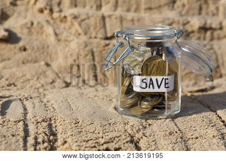 Coins in glass jar on rock background, copy space. Money box, saving money for dream, pension, vacation. Financial stability concept