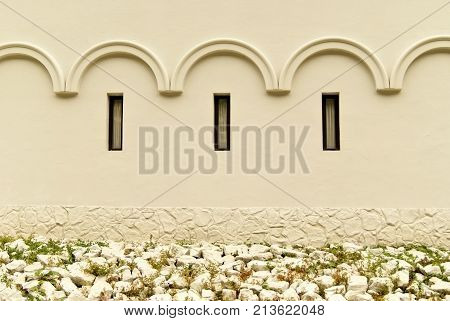 background: an old wall of a building or castle with a vaulted pattern and three glazed windows-loopholes