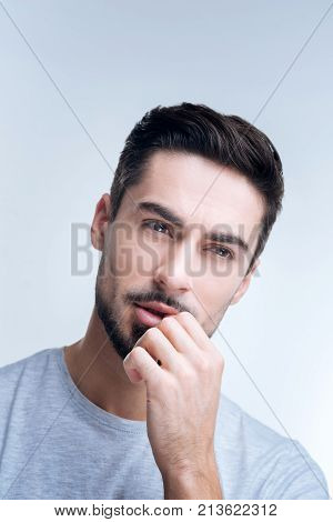 Difficult topic. Clever tired attentive student thinking about a difficult question at his exam while sitting with his hand touching the lips