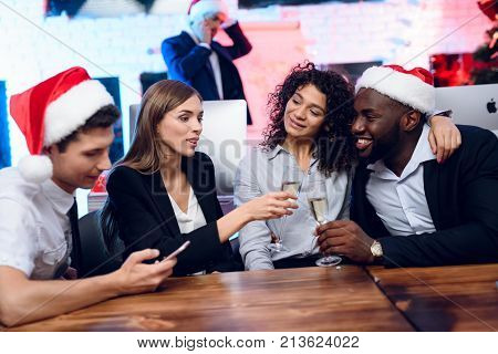 People Are Preparing To Meet The New Year In The Office. They Sit With Glasses Of Champagne In Their