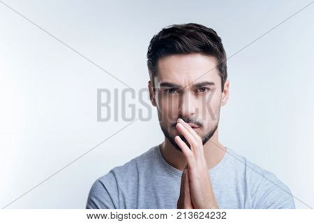 Looking upset. Nice handsome young man standing with his hands near his lips and looking upset after watching a depressive film