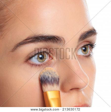 A girl with open eyes put a foundation cream brush under the eyes close-up on a white isolated background