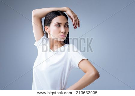 Calm ballerina. Serious attentive beautiful ballerina standing against the blue background and looking at her fingers while her arm being on her head