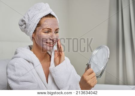 Attractive woman in a white towelling robe applying a face mask while looking in a handheld mirror as she pampers herself with a beauty treatment