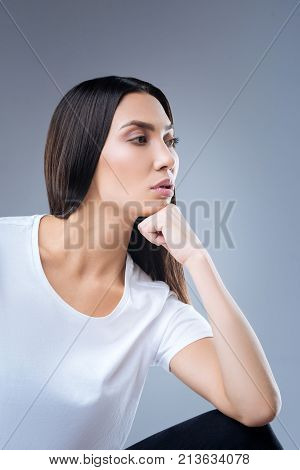 Strong housewife. Enthusiastic reliable strong woman sitting thoughtfully with her chin resting on her fist while preparing to clean the house