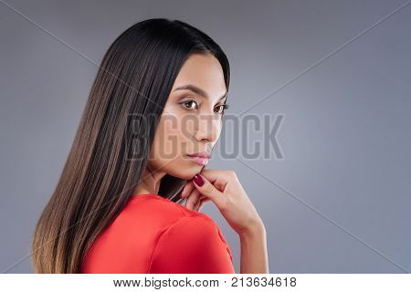 New concept. Clever responsible enthusiastic worker looking interested in the new strategy of development while standing thoughtfully with her fingers touching her chin