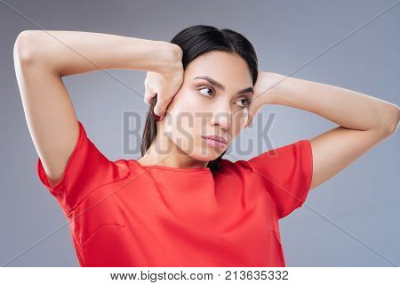 Noisy. Young irritated woman looking unpleased while hearing extremely loud sounds and closing her ears with her two hands