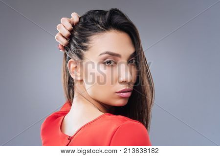 Passionate woman. Beautiful passionate woman looking into the distance while standing against the blue background with her hand on the head