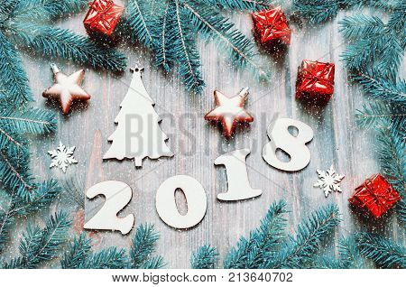 Happy New Year 2018 background with 2018 figures Christmas toys blue fir tree branches. New Year 2018 still life with snowflakes. Festive New Year 2018 greeting card. New Year 2018 holiday background