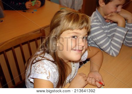 Schoolgirl Sits At A Desk And Smiles