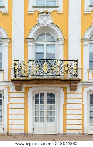 The vertical shot of Petrodvorets. Exterior of one classic building's wrought iron balcony and the front entrance
