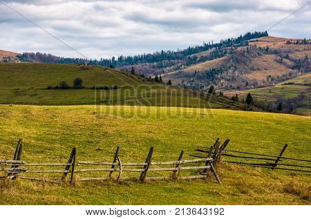 Wooden Fence On Grassy Rural Hill In Late Autumn