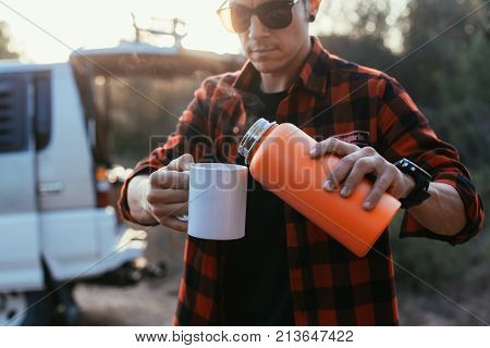 Trendy young man stands on camping site or on road stop in front of his camping van or camper with open trunk pours coffee or tea from flask thermos in mockup cup to warm up