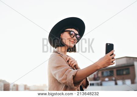 Cute and pretty fashion trendy and hipster millennial woman or girl makes selfie on smartphone camera to share on internet social media channels self absorbed new generation of young people