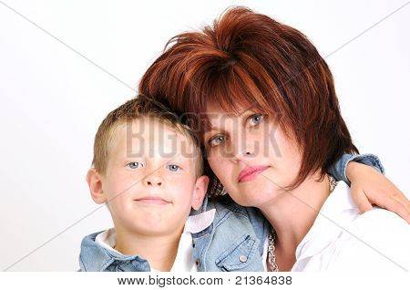 mother and teen son hugging and smiling smartly dressed