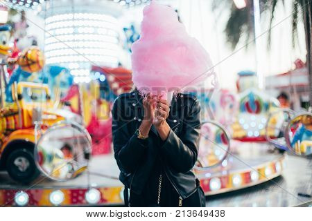Happy attractive and beautiful young woman or female teenager with blonde hair wears black leather jacket stands in front of attraction ride at festival or carnival and holds huge pink cotton candy