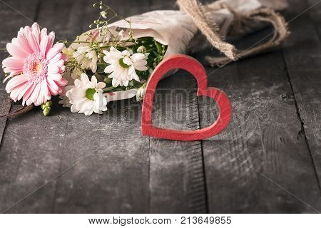 Flowers wrapped in newspaper and a heart - Selective focus image with a lovely bouquet of flowers wrapped in a newspaper and a red blur heart on a black wooden background.