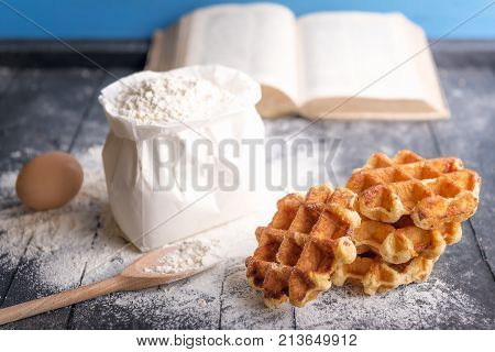 Fresh waffles and ingredients - Cooking theme image with a bunch of delicious Belgian waffles egg a bag of flour and an open cookbook on a rustic wooden table.
